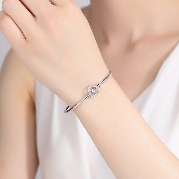 дамска ръка с твърда сребърна гривна с елемент под формата на щит и кубичен цирконий в средата