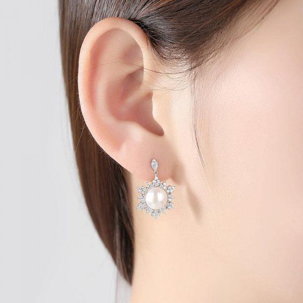 дамски модел носещ сребърни висящи обеци с масивна перла и заобикалящи я кубични циркони