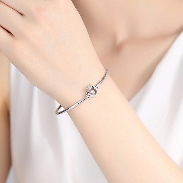 дамска ръка с твърда сребърна гривна под формата на сърце с изискан кубичен цирконий
