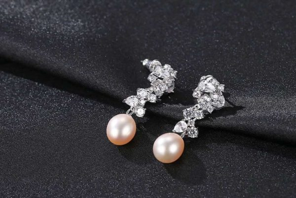Hanging earrings with pink pearls and a large number of cubic zircons photographed on a black surface