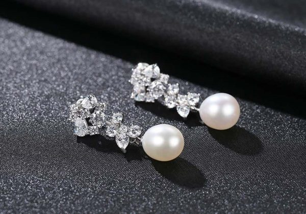 Hanging pearl earrings with a large number of cubic zircons photographed on a black surface