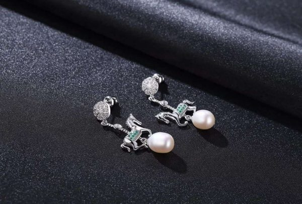 hanging silver earrings with a pendant in the form of a horse and a pearl under it photographed on a black surface