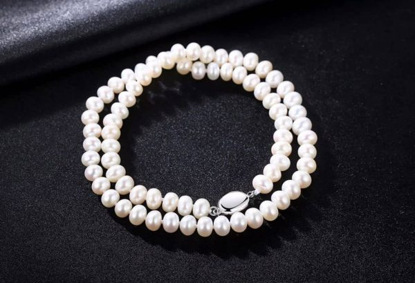clear pearl necklace with white pearls photographed on black surface