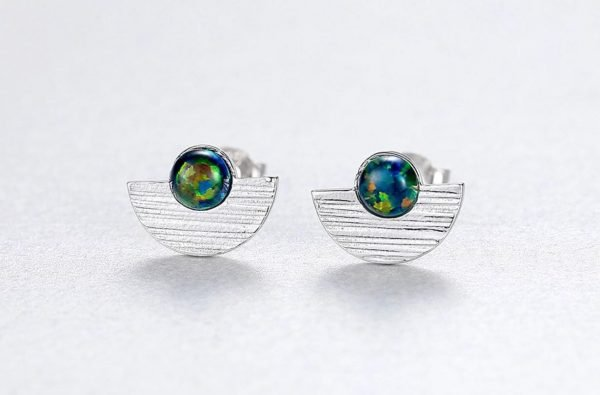 frontal shot of silver earrings with opal resembling the colours of the globe