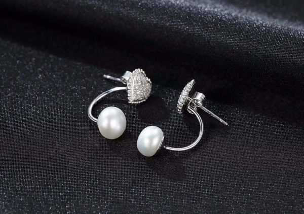heart-shaped silver earrings with cubic zirconia and pearl photographed at an angle on a black surface
