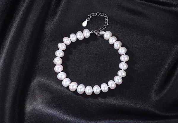 сребърна гривна с бели перли снимана отгоре върху черна повърхност