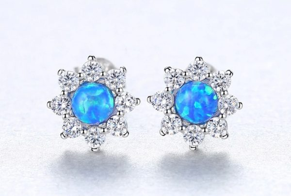 silver earrings with floral motif and blue opal in the center