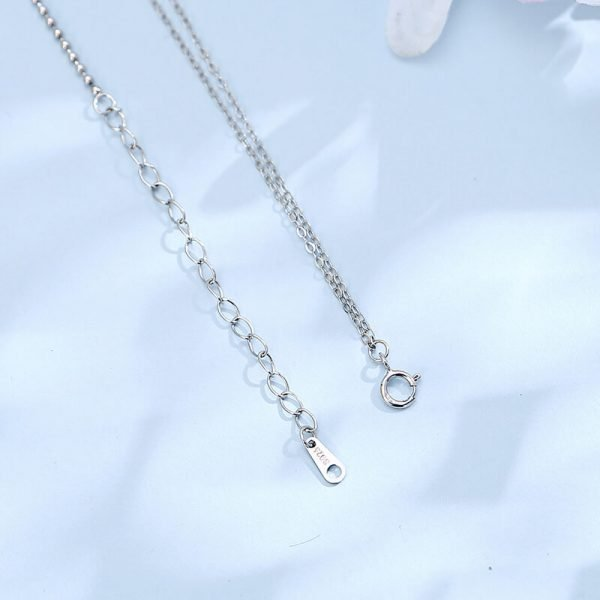 the clasp of a silver necklace with two types of braids on a light blue background