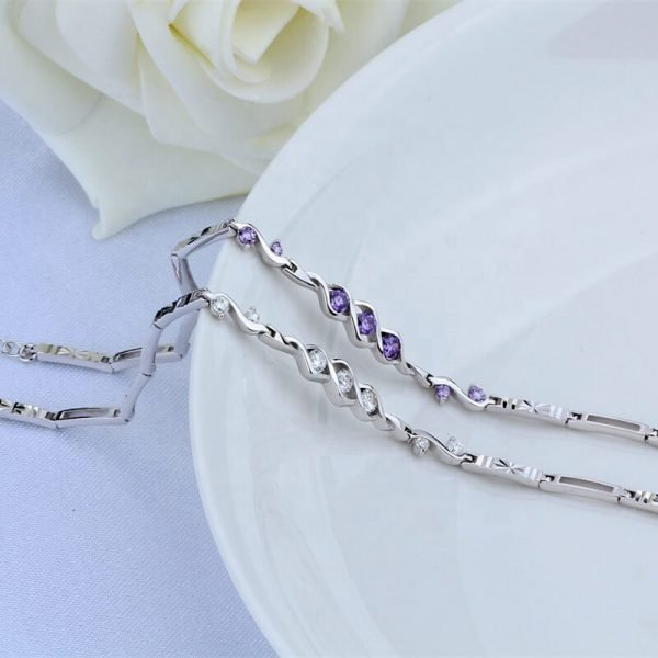 two sterling silver bracelets and 7 cubic zircons in two colours, photographed on a ceramic vessel