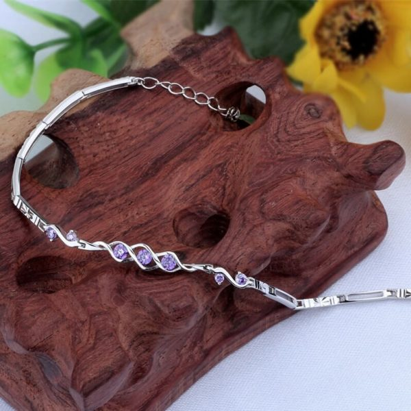 silver bracelet made of docked elements and 7 purple zircons, photographed unfastened on a wooden element