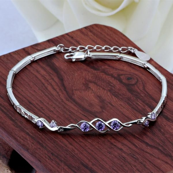 silver bracelet made of docked elements and 7 purple cubic zirconia - frontal photo on wooden element