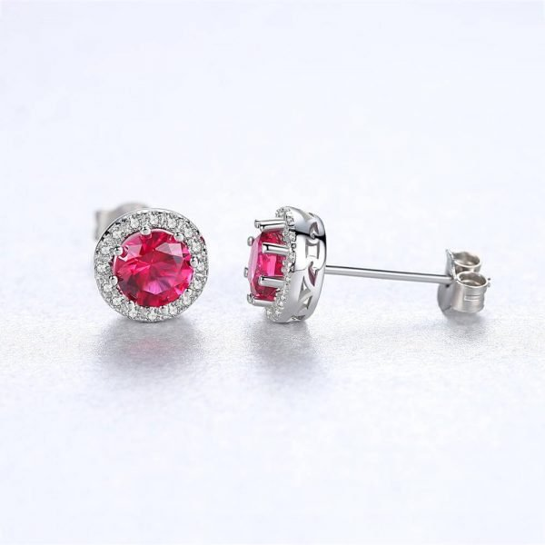 front and side of round silver earrings with massive ruby