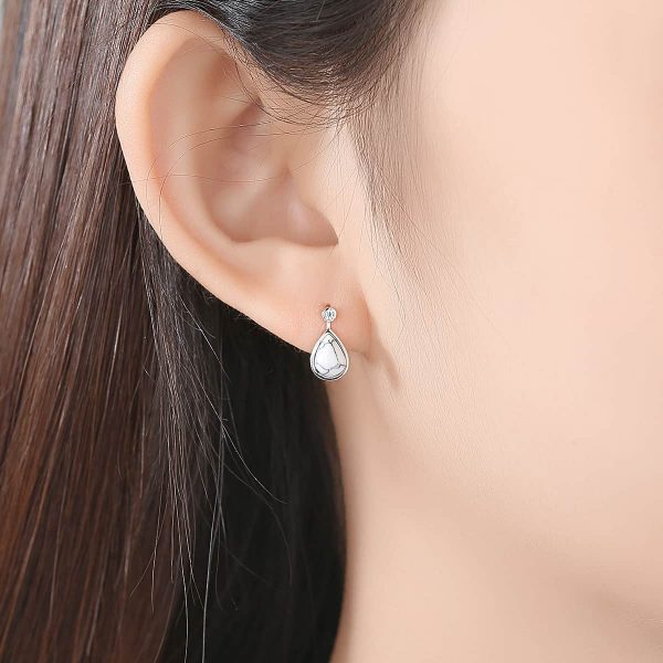 female ear with drop silver earring with turquoise stone