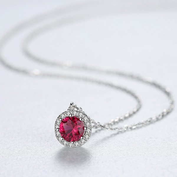 silver necklace with round pendant and red ruby in the center