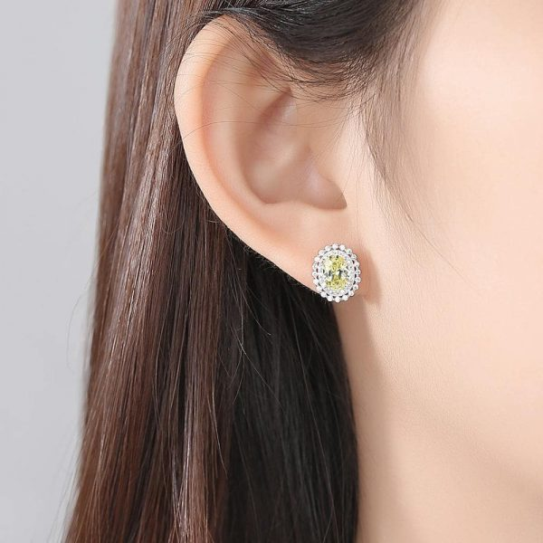 female ear with round silver earring with yellow synthetic topaz