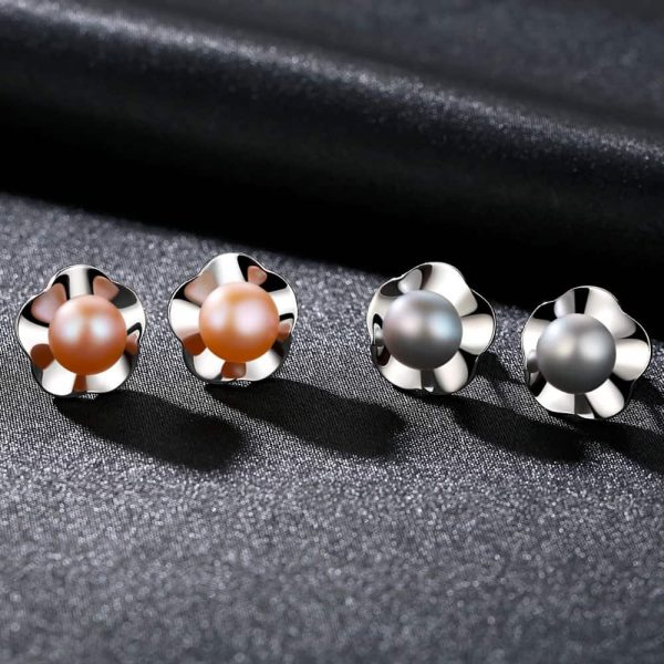 silver earrings with pearls in two colors and floral element behind them photographed on black fabric