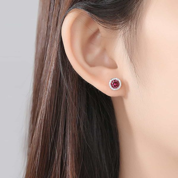 ladies ear with round silver earring with massive ruby