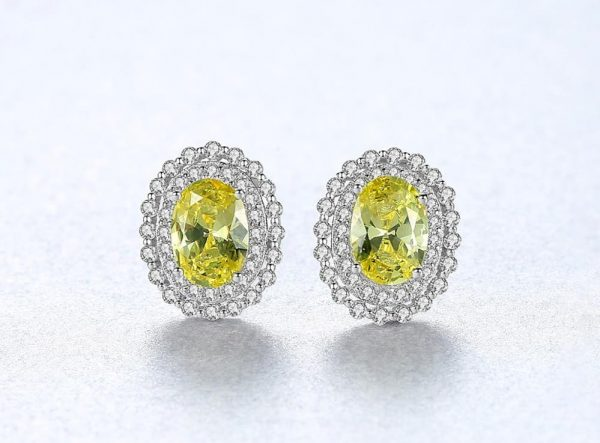 frontal close-up of elliptical silver earrings with yellow synthetic topaz