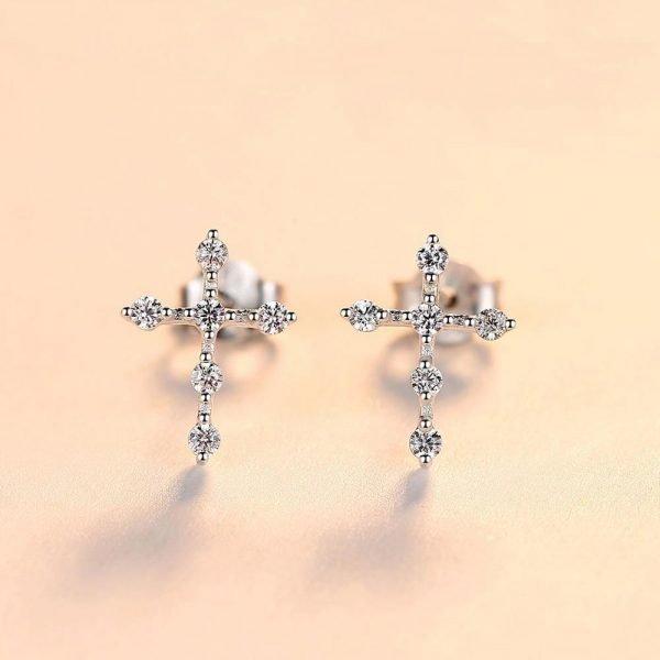 детайлна снимка на сребърни обеци във формата на кръст покрити с кубични циркони