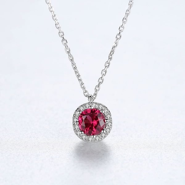 frontal shot of silver necklace with round pendant and red ruby in the center