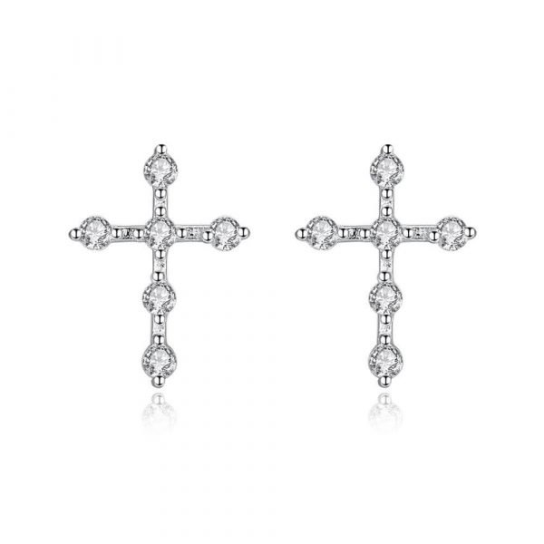 silver earrings in the shape of a cross covered with cubic zircons on a white background