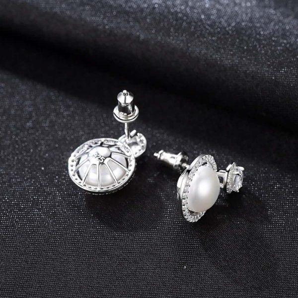 предната и странична страна на сребърни обеци с кръгъл кубичен цирконий и масивна перла под него снимани върху черен плат