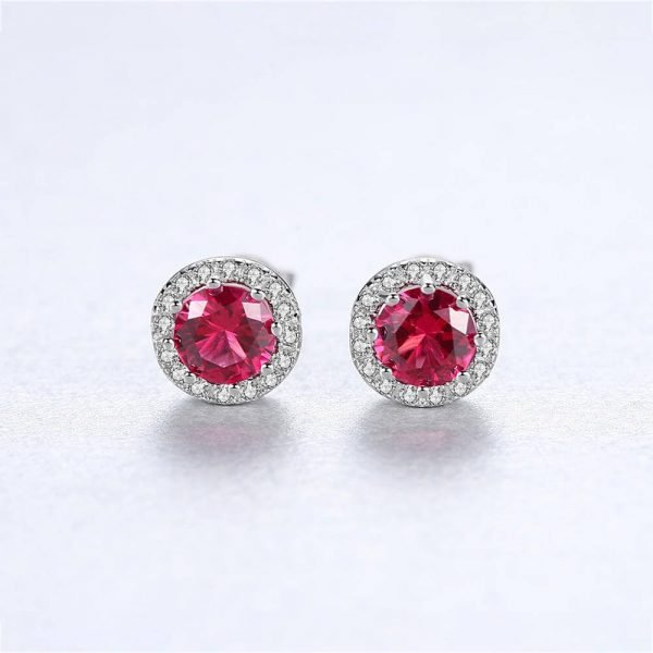 frontal close-up of round silver earrings with massive ruby