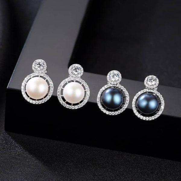 сребърни обеци с кръгъл кубичен цирконий и масивна перла в два различни цвята под под него снимани върху черен елемент