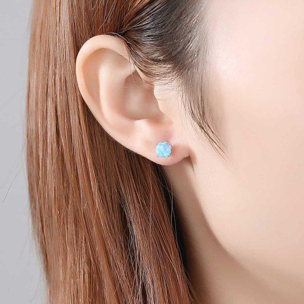 женско ухо със сребърна обеца на винт с кръгъл синтетичен опал