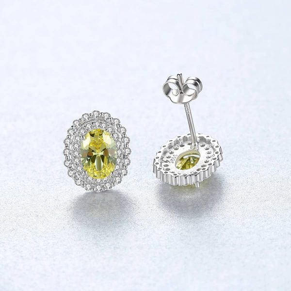 front and back of elliptical silver earrings with yellow synthetic topaz photographed on a light surface