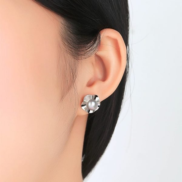 female ear with silver screw earring with light pearl