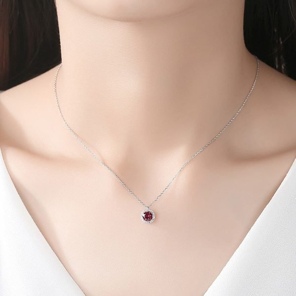 woman with silver necklace with round pendant and red ruby in the center