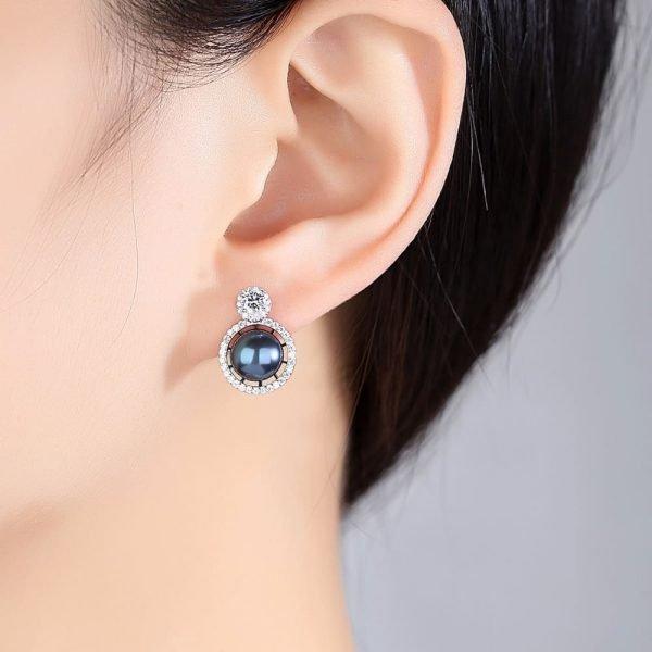 женско ухо със сребърна обеца с кръгъл кубичен цирконий и масивна таитянска перла под него