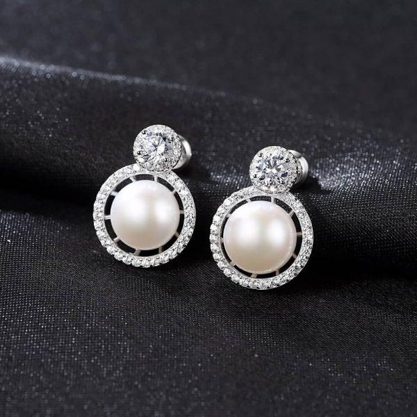 сребърни обеци с кръгъл кубичен цирконий и масивна перла под него снимани върху черен плат