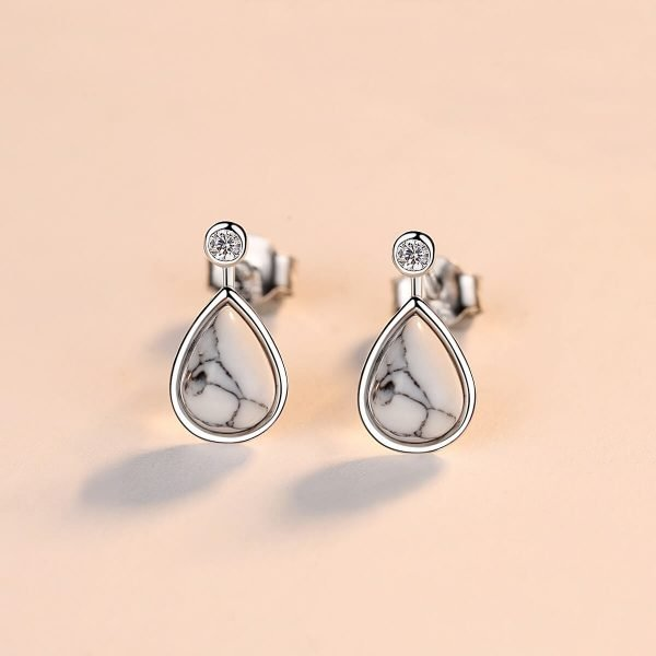 frontal photo of drop-shaped silver earrings with small cubic zirconia and turquoise photographed on a white surface