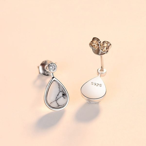 front and back of drop-shaped silver earrings with small cubic zirconia and turquoise photographed on white surface