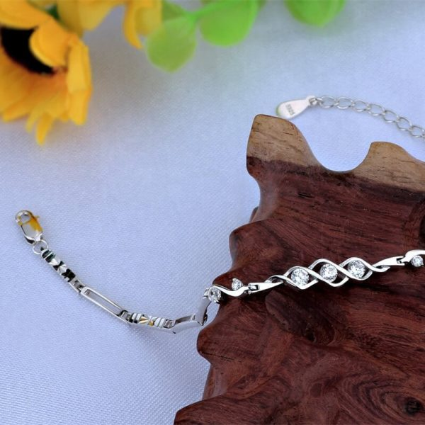 silver bracelet made of docked elements and 7 cubic zircons on a wooden element