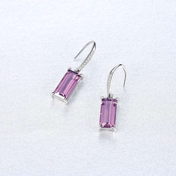 silver earrings with purple synthetic sapphire and hook type fastening photographed from above on a light surface