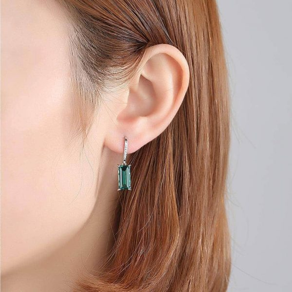 female ear with silver earring with green synthetic sapphire and hook type fastening