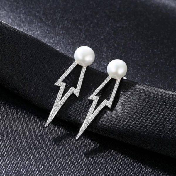 сребърни обеци под формата на стрела с бяла перла на върха снимани върху черен плат