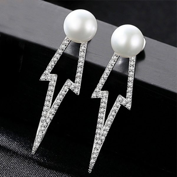 детайлна снимка на сребърни обеци под формата на стрела с бяла перла на върха върху черна повърхност