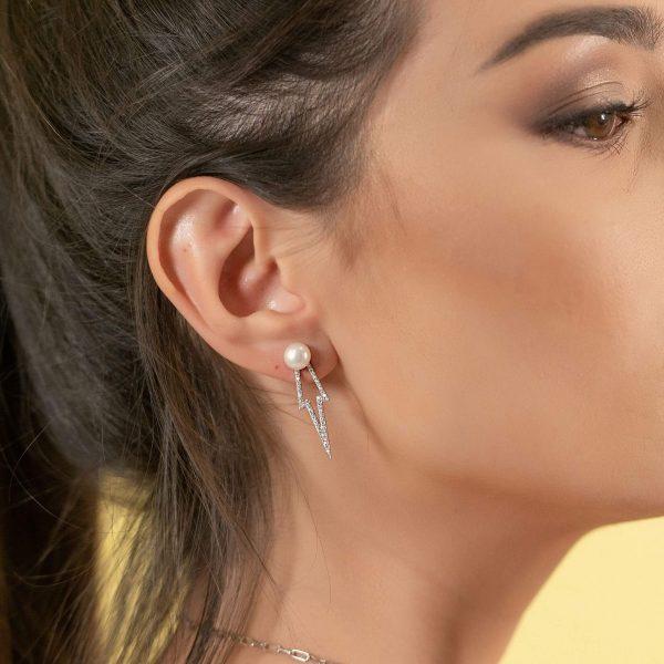 женско ухо със сребърна обеца под формата на стрела с бяла перла на върха