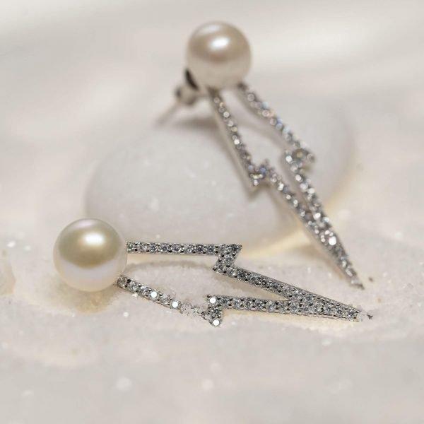 сребърни обеци във формата на стрела с камъни кубичен цирконий и перла снимани върху бял камък и бял пясък