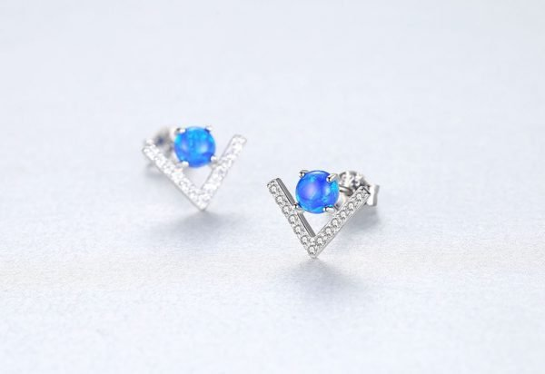 silver earrings in the shape of the letter V and round blue opal in the center - focus on one earring
