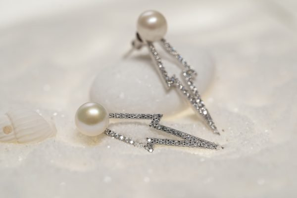 silver earrings in the form of an arrow with a beautiful pearl photographed detailed on a white background