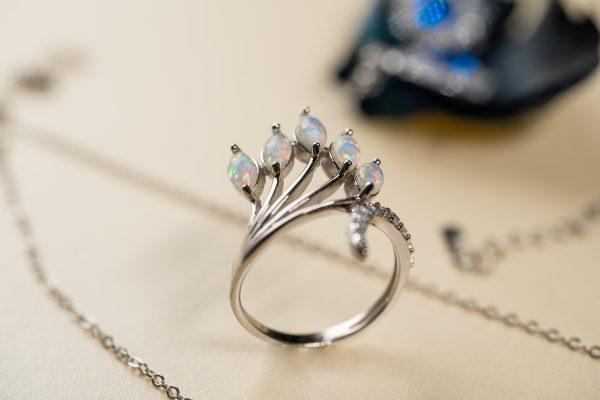 сребърен пръстен с пет камъка многоцветен синтетичен опал сниман отблизо на фокус