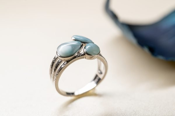 silver ring with three oval larimar stones photographed close up