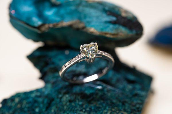 детайлна снимка на сребърен пръстен със сърцевиден камък и кубични циркони