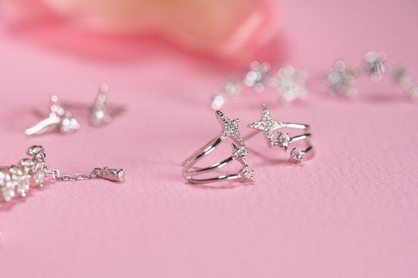 снимка с фокус върху сребърни обеци с три малки звездички снимани върху розова повърхност