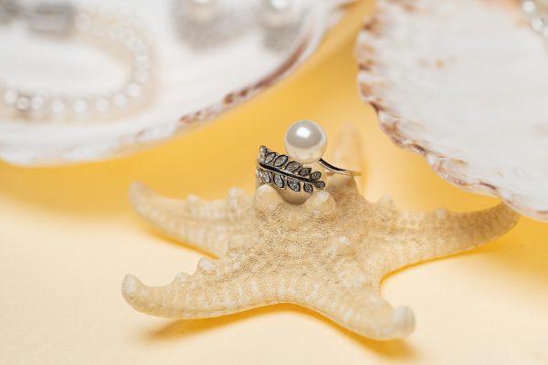 сребърен пръстен с флорален мотив и красива перла сниман върху морска звезда